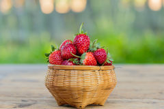 Ripe strawberries with leaves in wicker basket on wooden table o Royalty Free Stock Photography