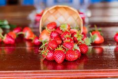 Ripe strawberries with leaves in wicker basket on wooden table o Royalty Free Stock Image