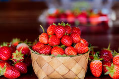 Ripe strawberries with leaves in wicker basket on wooden table o Stock Photography