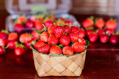 Ripe strawberries with leaves in wicker basket on wooden table o Stock Photo