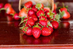 Ripe strawberries with leaves in wicker basket on wooden table o Stock Image