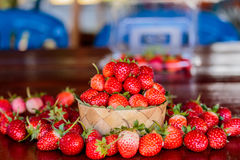 Ripe strawberries with leaves in wicker basket on wooden table o Royalty Free Stock Photos