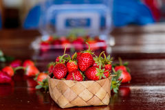 Ripe strawberries with leaves in wicker basket on wooden table o Royalty Free Stock Photo