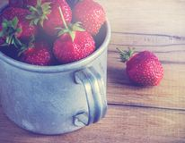 Ripe strawberries in a metal mug. Old wooden table Stock Images
