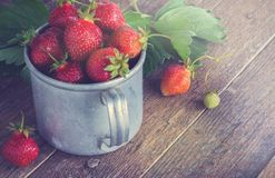 Ripe strawberries in a metal mug. Old wooden table Royalty Free Stock Photography