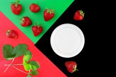 Ripe strawberries, milk and green leaves on a contrasting color background. Red, green, black Stock Photography