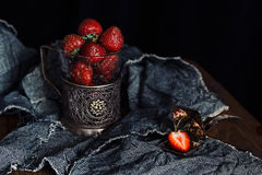 Ripe strawberries in old glass holder on dark rough fabrics background. Stock Photography