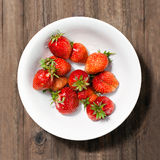 Ripe strawberries on the plate. Ripe red strawberries on the plate lies on a table made of wood Stock Photo