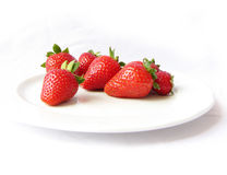 Ripe strawberries on plate. Closeup of ripe red strawberries on plate, isolated on white background Stock Photo
