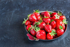Ripe strawberries on the plate on a concrete background. Ripe red strawberries in the iron plate on a dark concrete background Stock Images