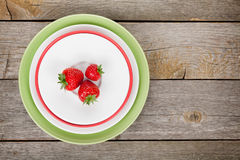 Ripe strawberries on plate over wooden table background Stock Photography