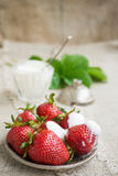 Ripe strawberries on a plate. Several large ripe strawberries with sour cream on a plate Stock Photos