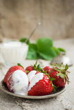 Ripe strawberries on a plate. Several large ripe strawberries with sour cream on a plate Royalty Free Stock Image
