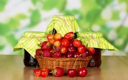 Ripe strawberries, raspberries, cherries in basket, jam on abstract green. Ripe strawberries, raspberries and cherries in a basket, jars of jam on abstract Stock Photo