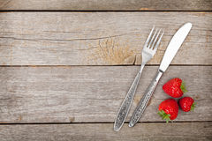 Ripe strawberries with silverware over wooden table background Royalty Free Stock Image