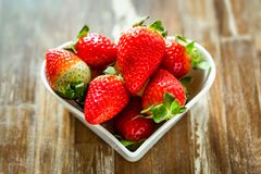 Ripe strawberries and tangerine slices. Tangerine slices, kiwi and strawberries in white plates in the shape of a heart against wooden table background stock images