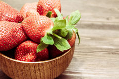 Ripe strawberries in wooden bowl with copy space and back light Royalty Free Stock Images