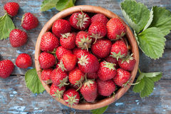 Ripe strawberries in wooden bowl and green leaves Royalty Free Stock Photo