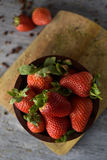 Ripe strawberries in a wooden bowl. High-angle shot of some appetizing ripe strawberries in a wooden bowl on a wooden chopping board, placed on a rustic wooden stock image