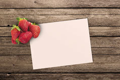 Ripe strawberry and a clean sheet paper. On a wooden table royalty free stock photos