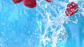 Ripe strawberry falling into water splash cascade in slow motion shot at 1500 fps.  stock video footage