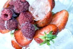 Ripe strawberry and frozen raspberry. In ice Stock Photo