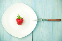 Ripe strawberry fruit on a white plate Stock Images
