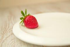 Ripe strawberry fruit on a white plate Stock Photos
