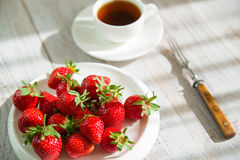 Ripe strawberry fruits on a white plate Royalty Free Stock Photos