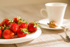 Ripe strawberry fruits on a white plate Stock Photo