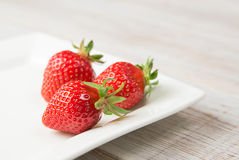 Ripe strawberry fruits on a white plate Royalty Free Stock Photo