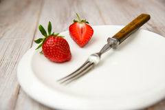 Ripe strawberry fruits on a white plate Royalty Free Stock Photography