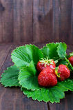 Ripe strawberry among the green leaves on a dark wooden table Royalty Free Stock Photo