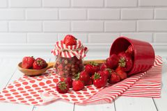 Ripe strawberry in jar and red pot Stock Image