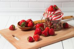 Ripe strawberry in jar and spoon Stock Image