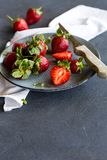 Ripe strawberry. Plate with some ripe strawberries over a grey textured background Stock Images