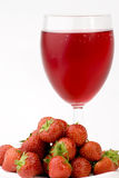 Ripe Strawberry's and glass of juice. Shot against a plain background Royalty Free Stock Image