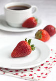 Ripe strawberry on a white plate and a cup of coffee on a white. Ripe strawberry on a white plate and a white cup of coffee on a white table Stock Photos