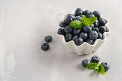 Ripe sweet blueberries in white bowl on a gray concrete background. Ripe sweet blueberries in white bowl on a gray concrete background, selective focus, copy Royalty Free Stock Image