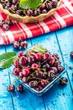 Ripe sweet cherries on blue woden table with water drops stock photo