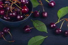 Ripe sweet cherry in a black bowl royalty free stock photo