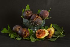 Ripe sweet figs with green leaves, mediterranean fig fruit. Royalty Free Stock Photo