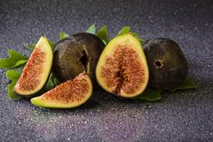 Ripe sweet figs with green leaves, mediterranean fig fruit. Stock Images