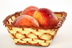 Ripe sweet peaches in wicker basket, isolated on white Stock Photo