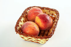 Ripe sweet peaches in wicker basket, isolated on white Stock Images