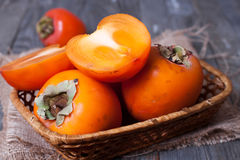 Ripe sweet persimmons, on wooden table. Ripe sweet persimmons on wooden table Stock Images