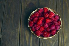 Ripe sweet raspberries in basket on wooden background. Ripe sweet raspberries in bowl basket on wooden background close up Stock Photos