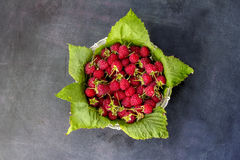Ripe sweet raspberries in bowl on dark background. Close up, top view. High resolution product Stock Photo
