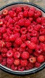 Ripe sweet raspberries in bowl on table close-up.  Royalty Free Stock Images