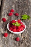 Ripe sweet raspberries in bowl on table close-up. Vertical Royalty Free Stock Photos